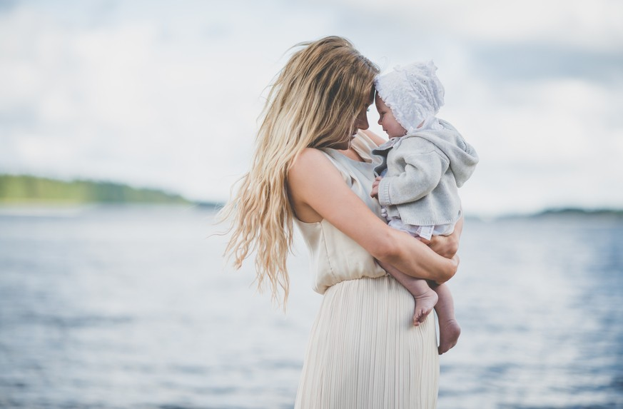young mother with her baby girl atthe beach