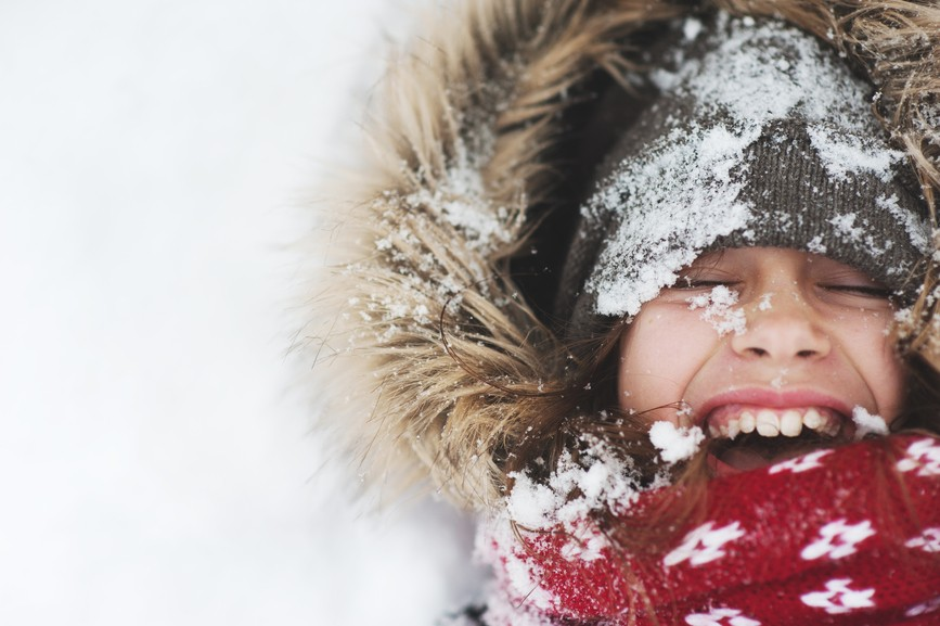 A cute young girl playing inthe snow