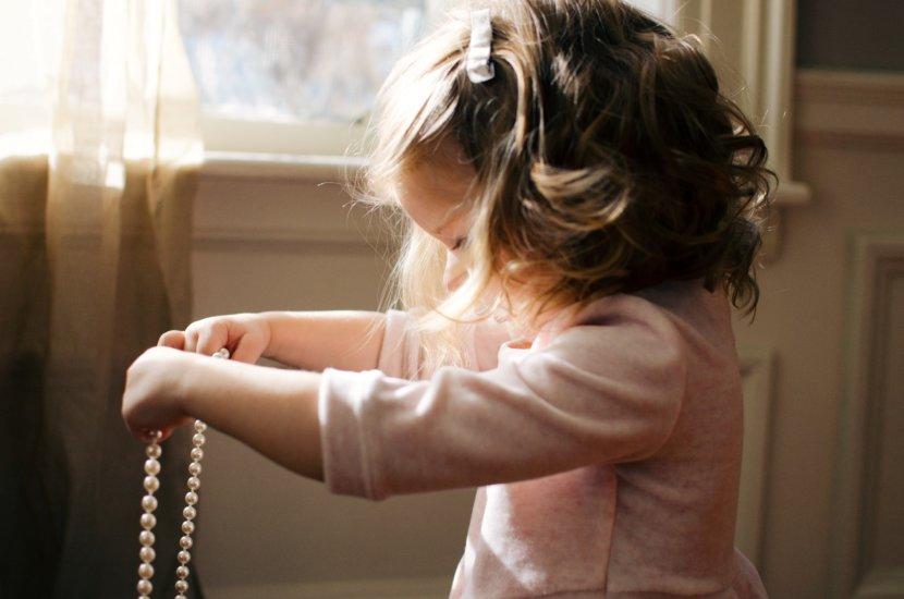 Dziewczynka bawi się koralami